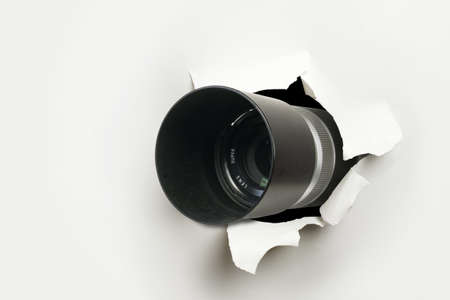 Concept of paparazzi or hidden camera, camera lens looks out through a hole in white paper wall Banque d'images