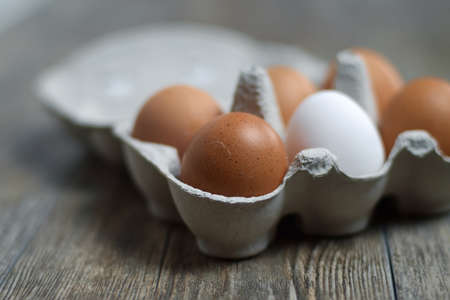 White egg between brown eggs in a paper tray on a wooden surface, focus point Banque d'images