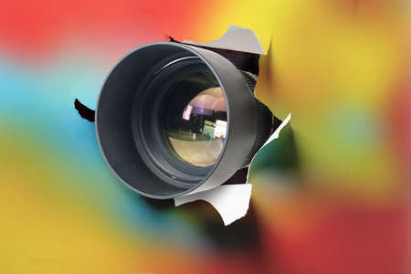 Concept of paparazzi or hidden camera, camera lens looks out through a hole in colorful background Banque d'images