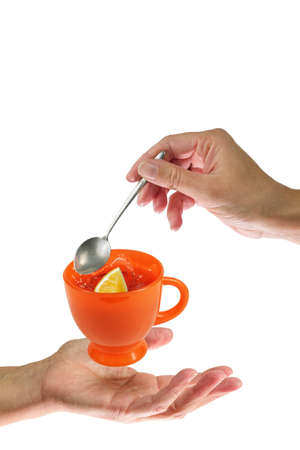 Levitating orange teacup betveen the woman's hands. Isolated on a white background