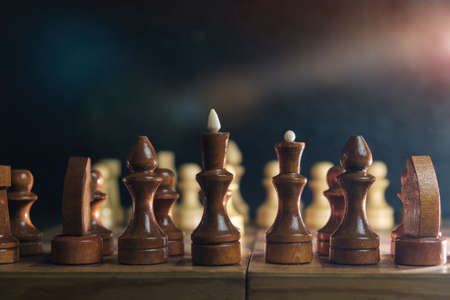 Wooden chess pieces and a chessboard on blurred dark background, selective focus