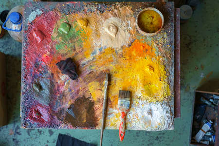 Wooden art palette with color paints and a brushes, top view