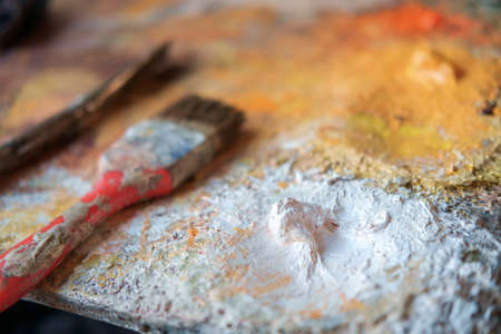 Detail of a wooden art palette with paints and a brush, selective focus Banque d'images