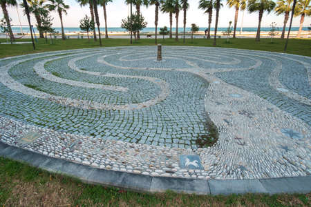 Tangled decorative path made with pebbles on the round stone cobblestone pavement at seaside park with palm trees Stockfoto