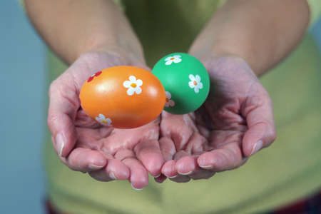 Hands of a woman perform a magic trick with the colorful Easter eggs.