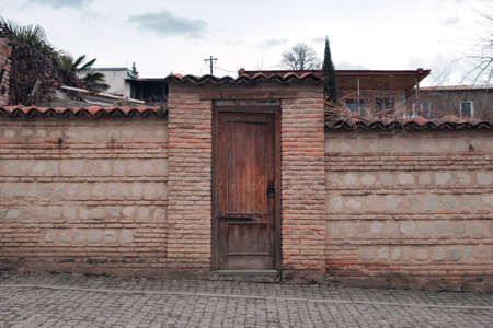 Wooden door with a round metal handle in the fence made with rocks and bricks