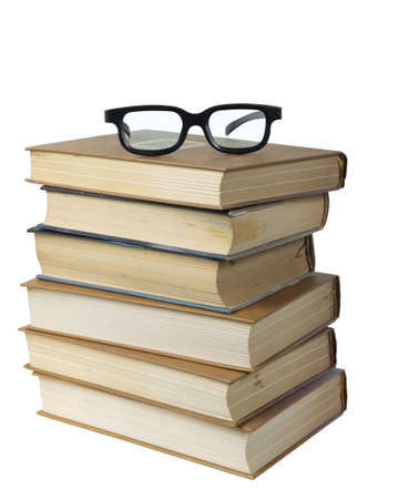 Eyeglasses on the top of the stack of books isolated on the white background