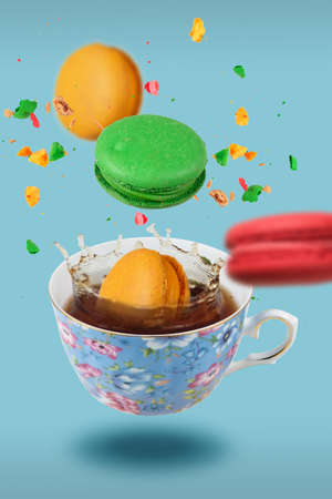 Color French macaroons falling in to the decorated blue porcelain teacup full of tea, selective focus 版權商用圖片