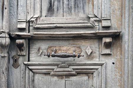 Old metal door handle on old wooden shabby brown door 版權商用圖片