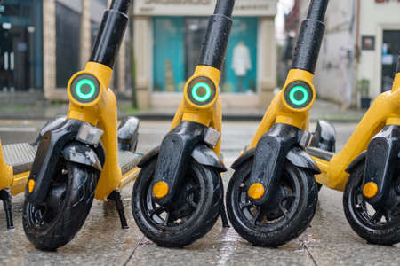 Yellow electric scooters covered with rain drops at the street, selective focus 版權商用圖片