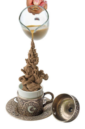 Coffee pouring from the pot in the coffee metal cup , isolated on a white background 版權商用圖片