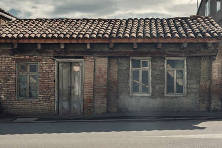 Facade of the old abandoned wrecked house with tile roof 版權商用圖片