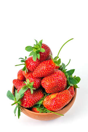 Group of fresh strawberries in the clay bowl, isolated on a white background