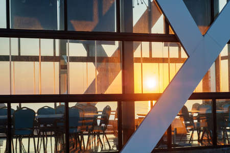 Sunlight shines through a glass wall of a building on the coast, beautiful sunset sky and sea background