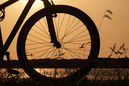 Close-up silhouette of a bike wheel at sunset. The sun shines through the frame of a bicycle, selective focus