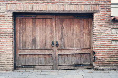 Old wooden gate with a large round metal handles