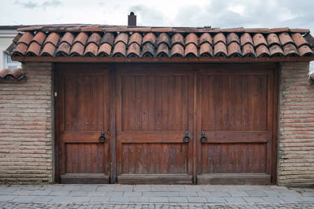 Old wooden gate with a large round metal handles and tiled roof