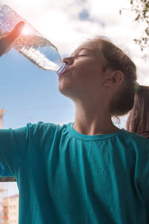 A girl in blue shirt drinking water from the bottle