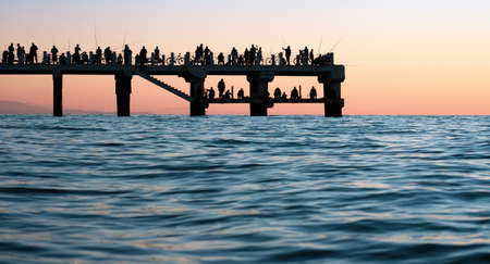 Silhouettes of the people fishing and enjoying the sunset over sea on a pier 版權商用圖片