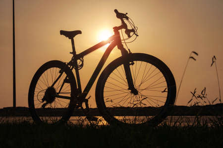 Silhouette of a bike at sunset. The sun shines through the bicycle frame at the coast