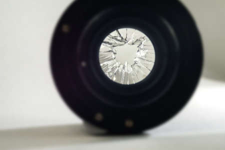 Broken camera lens with blurred background, selective focus