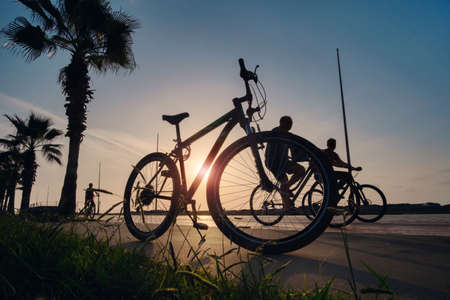 Silhouette of a bike at sunset. The sun shines through the bicycle frame with silhouettes of bicycle rider at sea side park 版權商用圖片