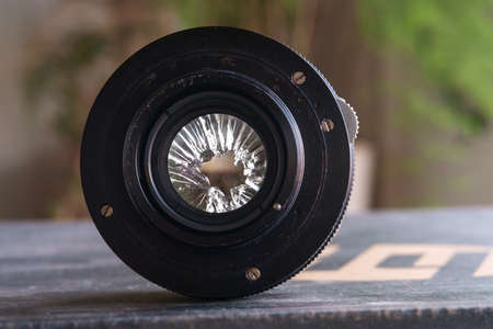 Broken camera lens with blurred nature background, selective focus 版權商用圖片