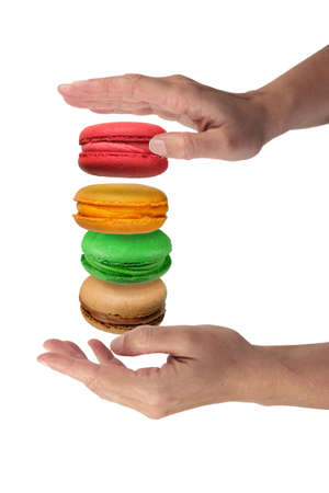 Hand holding stack of colorful French macaroons isolated on a white background 版權商用圖片