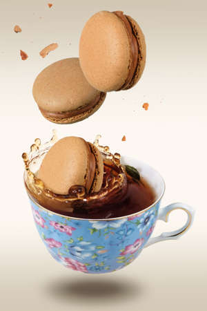 Brown French macaroons falling in to the decorated blue porcelain teacup full of tea, selective focus