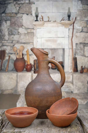 A traditional Georgian wine jug and clay cups on the grunge wooden table in marani (cellar for storing wine in special pitchers)