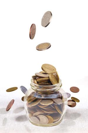 Money coins rain falling down in to the glass jar 版權商用圖片