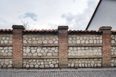 Fence made with rocks and bricks on a pavement