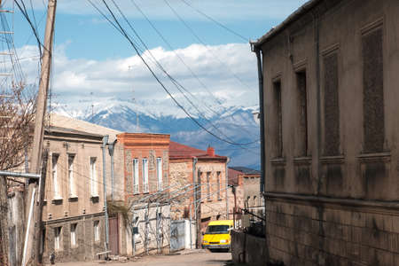 Narrow street in the town with snowy mountains background