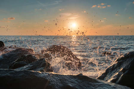 Sea waves crushing over the big rocks with beautiful sunset sky background 版權商用圖片