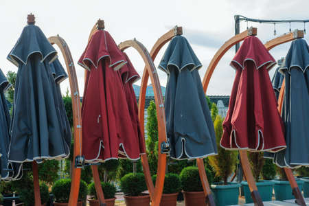 Large fabric closed red and blue sun umbrellas with potted plants 版權商用圖片