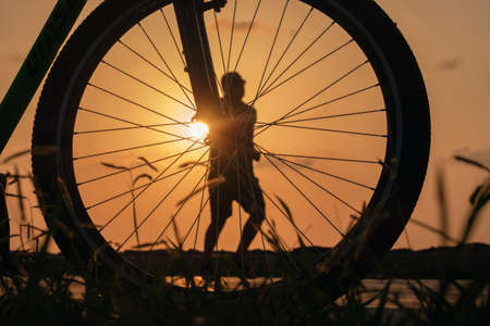 Close-up silhouette of a bike wheel at sunset. The sun shines through the wheel of a bicycle with blurred  runner figure at background