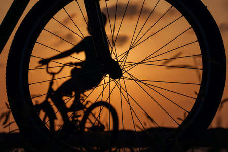 Close-up silhouette of a bike wheel at sunset. The sun shines through the wheel of a bicycle with blurred  bicycle rider figure