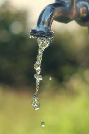 Pouring fresh water  from the metal tap with blurred nature background, selective focus
