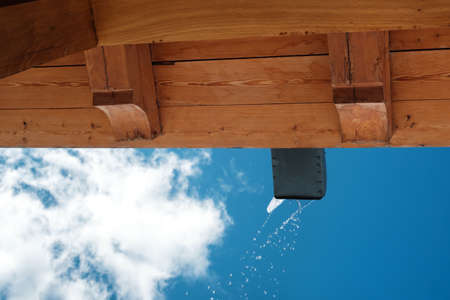 Melted water is pouring from the draining gutter with blue sky background 版權商用圖片