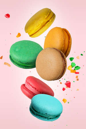 Colorful French macaroons falling or flying in motion on a light pink background 版權商用圖片