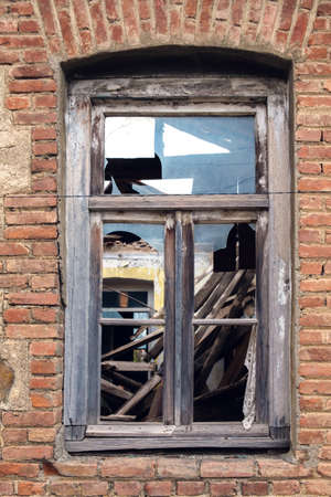 Vintage window in brown wooden frame and broken glass on red brick wall 版權商用圖片