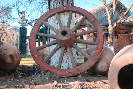 Wooden red wheel from an ancient cart standing in front of the tree at the yard