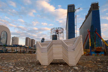 Beach chaise lounges stacked in a row on the shore with cityscape and blue cloudy sky background 版權商用圖片
