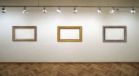 Interior of a white wall with frames and spot lights at art gallery