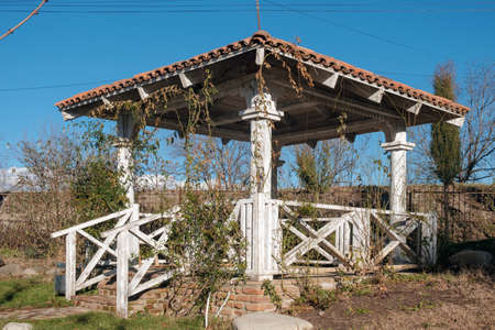 White wooden gazebo in the garden overgrown with plants on the blue sky background 版權商用圖片