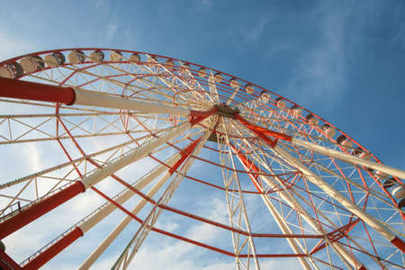 A large red and white Ferris Wheel against a blue sky