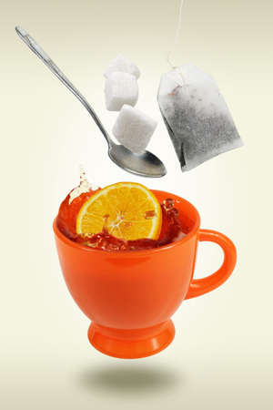 Levitating orange teacup with flying teabag, spoon and sugar cubes