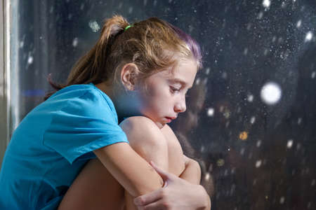 A brown eyed girl in blue t-shirt sitting on the window sill behind a foggy window with snowy night background