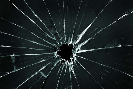 The hole in the broken and cracked glass, closeup on dark background