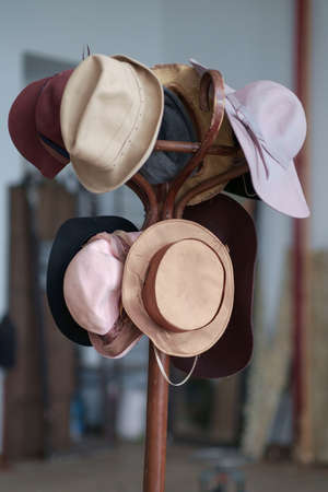 A variety of vintage colorful hats hanging on the wooden brown coat rack, selective focus